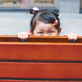 Cute girl little hiding behind the wooden bench Stock Photos
