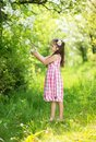 Cute girl little is holding flower outside in the green park Stock Photo