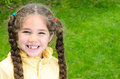 Cute girl with long hair braids smiling and missing tooth smiles to the camera while being outdoors on a grassy field in the Royalty Free Stock Image