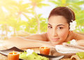 Cute girl on massage table outdoors closeup portrait of brunet lying down tropical beach luxury spa resort alternative therapy Stock Photo