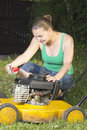 Cute girl oiling and repairing yellow lawn mower Stock Photography