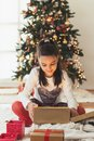 Cute girl opening a present on a Christmas morning Royalty Free Stock Photo
