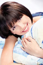 Cute girl on pillow smiling short hair Stock Photos