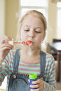 Cute girl playing with bubble wand at home Royalty Free Stock Photo