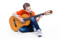 Cute girl plays on the acoustic guitar sitting and isolated white background Stock Image