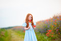 A cute girl in poppy field of flowers in the open air. The girl Royalty Free Stock Photo