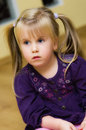 Cute girl portrait with pigtails of a little in a purple dress and Royalty Free Stock Photography