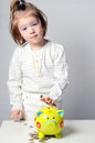 Cute girl putting her savings to a piggy bank bankearly concept Royalty Free Stock Photo