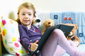Cute girl reading a book on her bed with toys around her Royalty Free Stock Photo