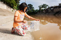 Cute  girl release fish into the canal Royalty Free Stock Photo