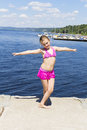 Cute girl on the riverbank in pink swimsuit dancing Royalty Free Stock Image