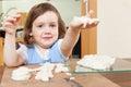 Cute girl sculpts dough figurines