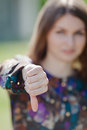 Cute girl showing thumb down focus on foreground attractive young woman open air Royalty Free Stock Photo