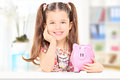 Cute girl sitting at table and holding a piggybank at home Royalty Free Stock Photography