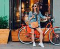 Cute girl in a summer dress, denim jacket, sunglasses and bag stands with red vintage bicycle in LA city, California Royalty Free Stock Photo
