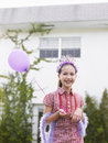 Cute girl in tiara and feather boa with balloon portrait of a young holding Royalty Free Stock Images