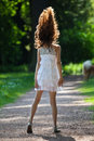 Cute girl tossing the hairs up on a forest path her in backlit Royalty Free Stock Images