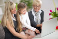 Cute girl using laptop with mom and grandma typing on while looking that Royalty Free Stock Images