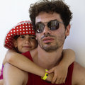 Cute girl wearing Panama hugs her serious father Stock Photography