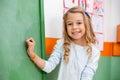 Cute girl writing on board in kindergarten portrait of little Stock Image