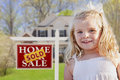 Cute girl in yard with sold for sale real estate sign and house smiling front Royalty Free Stock Photo