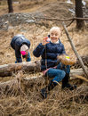 Cute girls having Easter egg hunt at forest at cold april day