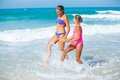 Cute girls on summer vacation friends running together in the beach shore Stock Images