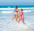 Cute girls on summer vacation friends running together in the beach shore Stock Photo
