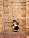 Cute graduation girl doll standing on brick background