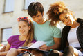 Cute group of teenages at the building of university with books huggings diversity nations Stock Photos