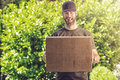 Cute guy with a happy grin making a delivery bearded in peaked cap exuberant of large brown cardboard box carrying it in his Stock Photos