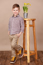 Cute handsome boy on a wooden floor with flowers in basket wearing stylish shirt trousers and boots.