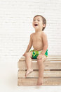 Cute handsome toddler laughing while sitting on wooden box Royalty Free Stock Photo