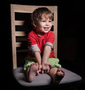 Cute happy baby boy sitting on chair dark background Stock Photography