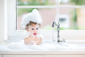 Cute happy baby girl playing with foam in kitchen sink Royalty Free Stock Photo