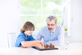 Cute happy boy playing chess with his grandfather in a white room Royalty Free Stock Images