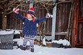 Cute happy child girl having fun and throwing snow in winter garden red blue knitted hat Stock Photos