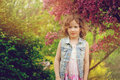 Cute happy child girl in jeans vest enjoying spring near blooming crab apple tree in country garden Royalty Free Stock Photo