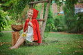 Cute happy child girl playing little red riding hood in summer garden with basket and flowers Royalty Free Stock Photo