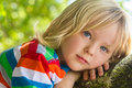 Cute, happy child relaxing deep in thought outdoors Royalty Free Stock Photo