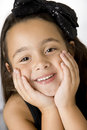 Cute happy girl six yr old hands on face with smile black ribbon in her hair Stock Images