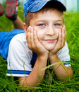 Cute happy kid laying on grass outdoor Stock Images