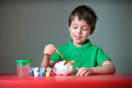 Cute happy little boy painting his piggy toy Stock Photography