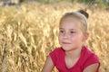 Cute happy little girl dreaming in wheat field Royalty Free Stock Photo