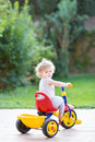 Cute happy smiling baby girl riding her first bicycle in the back yard of house Royalty Free Stock Photo
