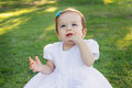 Cute happy smiling little baby girl in white dress scratching first teeth Royalty Free Stock Photo