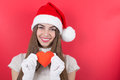 Cute happy teenage girl with santa hat showing paper heart caucasian beanie red smiling looking at camera against red background Royalty Free Stock Photography