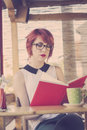 Cute hipster teenage girl reading a book and enjoying coffee retro styled imagery Stock Photography