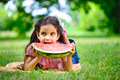 Cute hispanic girl eating watermelon at park Stock Photos