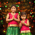 Cute indian girls greeting dressed in sari with folded hands representing traditional standing inside a temple celebrating Royalty Free Stock Photo